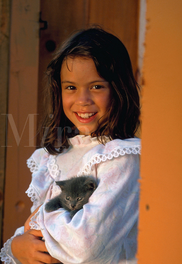 Portrait of smiling Hispanic girl holding her kitten.