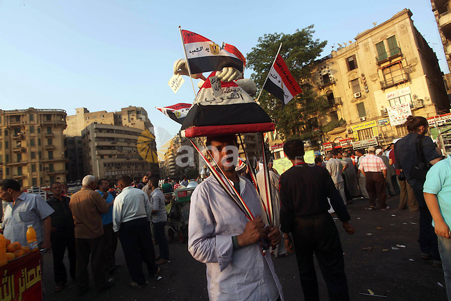 An Egyptian protester holds a hat in the shape of a pyramid bearing Egyptian flags and pro-democracy slogans during a demonstration against Egyptian presidential candidate Ahmed Shafiq in Tahrir Square decrying the result of the first round of voting in the Egyptian presidential election in Cairo, Egypt, Friday, June 1, 2012. Several hundred protesters rallied Friday in Cairo's Tahrir Square, the birthplace of the Egyptian uprising. Photo by Ashraf Amra