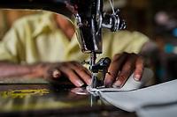 A Salvadoran shoemaker works on a sewing machine, stitching shoe uppers, in a shoe making workshop in San Salvador, El Salvador, 16 November 2016.