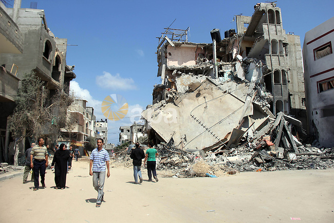 Palestinians walks past the remains of house, which witnesses said was hit by an Israeli air strike, in Nuseirat refugee camp in the central Gaza Strip on August 9, 2014. Israel launched more than 20 aerial attacks in Gaza early on Saturday and militants fired several rockets at Israel in a second day of violence since a failure to extend an Egyptian-mediated truce that halted a month long war earlier this week. The Israeli military said that since midnight it had attacked more than 20 sites in the coastal enclave where Hamas Islamists are dominant, without specifying the targets. Medical officials in Gaza said two Palestinians were killed when their motorcycle was bombed and the bodies of three others were found beneath the rubble of one of three bombed mosques. The air strikes which lasted through the night also bombed three houses, and fighter planes also strafed open areas, medical officials said. Photo by Khaled al-Sabbah