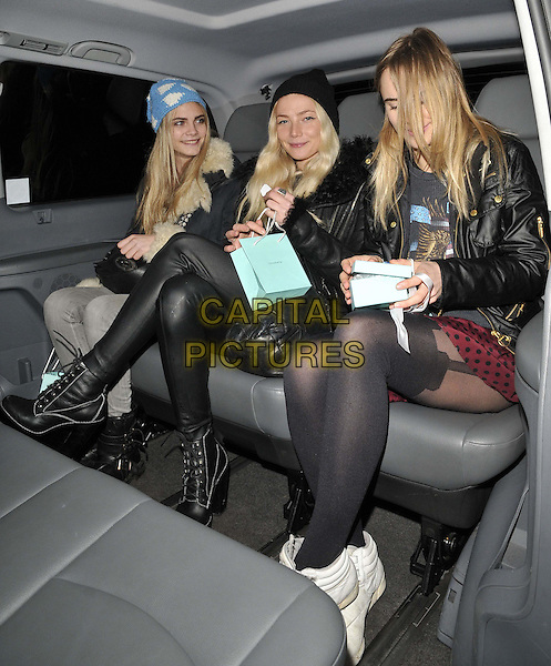 Cara Delevingne, Clara Paget & Suki Waterhouse .Tiffany & Co presents the Winter party celebrating the opening of 'Skate at Somerset House' Ice Rink, London, England..November 21st 2011.full length black blue white print knitted beanie hat sheepskin cuffs black coat jacket jeans denim grey gray boots leather tights sitting car legs thighs tights.CAP/CAN.©Can Nguyen/Capital Pictures.
