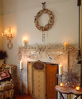 In the living room every available surface has been covered in Christmas decorations with a contemporary wreath on the wall above the fireplace
