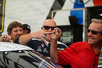 Jun 10, 2017; Englishtown , NJ, USA; Team owner Don Schumacher (right) pulls a championship ring off the finger of Wayne Waite a crew member for NHRA top fuel driver Antron Brown as they prepare to take a group photo in the pits during the Summernationals at Old Bridge Township Raceway Park. Mandatory Credit: Mark J. Rebilas-USA TODAY Sports