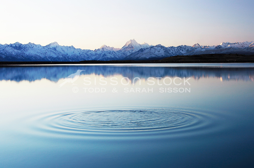 A stone's ripples on the tekapo to pukaki canal after sunset.   Aoraki Mount cook is reflected in the pond while the southern alps are shown in their full beauty..