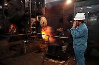 Workers operate on the old assembly line that was built in the 1960s to make train carriage wheels at Ma Steel in Maanshan, China on 29 December 2008. With an additional plant that opened last year, Ma Steel is the world's largest producer of train carriage wheels with an annual capacity of 1.1 million units. .
