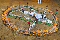 Diana R., who claims to be possessed by spirits, lies in a ring of fire during a ritual of exorcism performed by Hermes Cifuentes in La Cumbre, Colombia, 28 May 2012. Exorcism is an ancient religious practice of evicting spirits, generally called demons or evil. Although the formal catholic rite of exorcism is rarely seen and must be only conducted by a designated priest, there are many pastors and preachers in Latin America performing exorcism ceremonies. The 52-year-old Brother Hermes, as the exorcist calls himself, claims to have been carrying out the healing rituals for more than 20 years. Using fire, dirt, candles, flowers, eggs and other natural-based items, in conjunction with Christian religous formulas, he attempts to drive the supposed evil spirit out of a victim's mind and body.