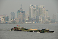 A barge crossing the Huangpu river in front of Pudong..Shanghai, February 2006.