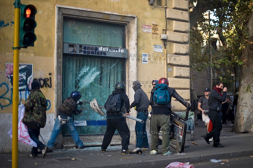 Alcuni black bloc sfondano una vetrina blindata di una banca..Protesters break the window of a bank