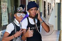 Cuba, Havana.  Young Cuban Couple Using a Public Pay Telephone.