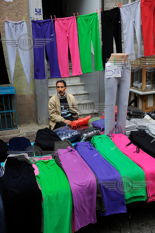 Clothing seller waiting for customers at a weekly market in Kumkapi district, an area with many cheap lodgings for traders and migrants from developing countries.