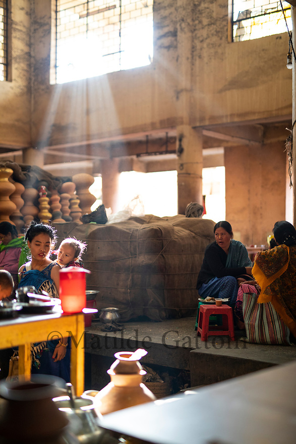 India - Manipur - Imphal - A ray of light enters the Ima Market at the end of the day while clients sit in food stalls and enjoy a hot cup of masala tea.
