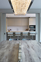 A set of sliding doors leads from the dining room area to a stylish, uncluttered kitchen decorated in neutral tones. The dining table which seats 10 is made of a bleach wood with bespoke aluminium legs. The contemporary chandelier light fitting is full of clear baubles which creates a stunning effect when lit.