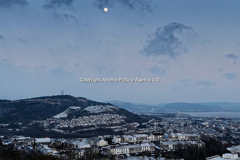 "Pictured: The lunar phonomenon known as Black Moon is seen over the St Thomas area of Swansea where snow caused by the ""Beast from the East"" has covered it in Swansea, south Wales, UK. Wednesday 28 February 2018<br /> Re: Strong cold winds from the east have been affecting most parts of the UK with temperatures in some parts below zero."