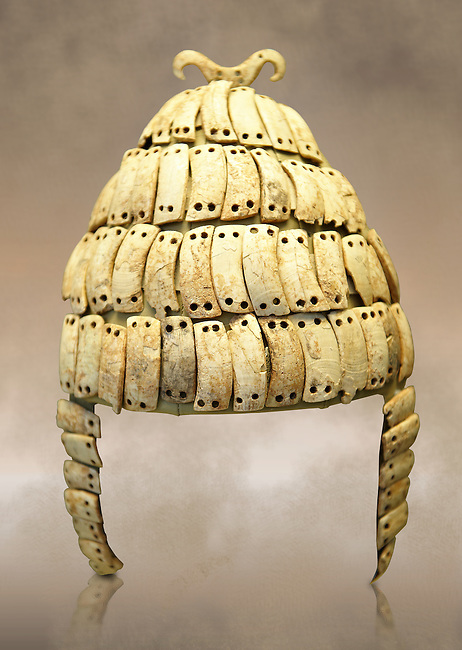 "Boar's tusk helmet with cheek guards and double bone hook on top. Tomb 515 Mycenae, Greece. 14th-15th century BC. National Archaeological Museum, Athens.. The Boar's tusk helmet was described in the Iliad as follows ""Meriones gave Odysseus a bow, a quiver and a sword, and put a cleverly made leather helmet on his head. On the inside there was a strong lining on interwoven straps, onto which a felt cap had been sewn in. The outside was cleverly adorned all around with rows of white tusks from a shiny-toothed boar, the tusks running in alternate directions in each row..?Homer, Iliad 10.260-5"""