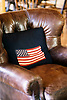 Crocheted cushion, featuring the American flag, on a plush leather lounge chair.