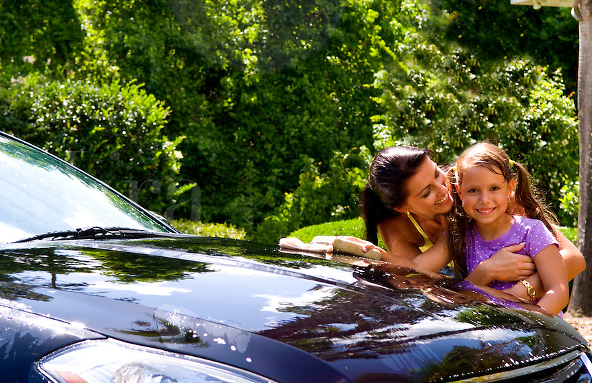 Mother and daughter hugging with love and washing car at home all wet and relaxing