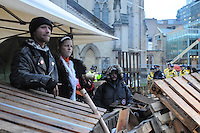November 23, 2011, Toronto Police deployed in significant numbers this morning, beginning the process of evicting the Occupy Toronto tent camp from St. James Park.  Here, two unidentified protest supporters hold their ground at their sacred fire tent as police look on in the distance.