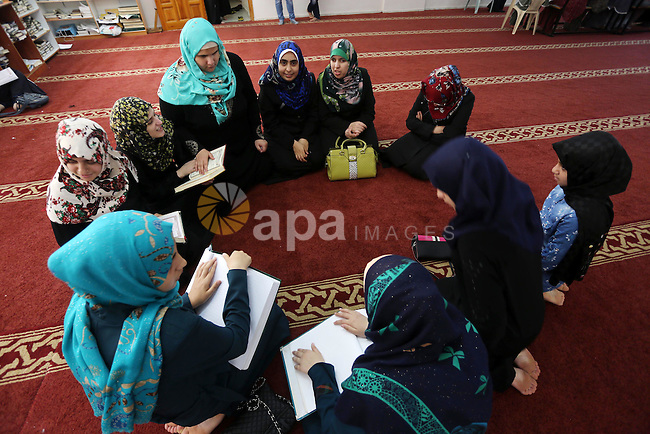 Palestinian blind girls read a copy of the Koran, Islam's holy book, at a religion school in Gaza City on June 21, 2016, during the Muslim fasting month of Ramadan. Photo by Mohammed Asad