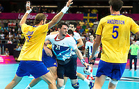 31 JUL 2012 - LONDON, GBR - Chris McDermott (GBR) of Great Britain (second from left) looks for a way through Sweden's defence during the men's London 2012 Olympic Games Preliminary round match at The Copper Box in the Olympic Park, in Stratford, London, Great Britain (PHOTO (C) 2012 NIGEL FARROW)