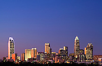 Downtown buildings in the Charlotte NC skyline take on a brilliant glow as they reflect the setting sun. Photo is part of a series of images taken during a 90-minute time period, which captures the sky turning from shades of brilliant colors as the sun set. Buildings shown in photo include the Duke Energy headquarters (far left), Wells Fargo buildings (middle), Bank of America tower (tallest on right) and Hearst Tower (tall far right).