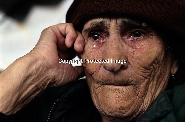 An old ethnic Albanian refugee woman weeps as she arrives in Kosovo on April 15, 1999 in Kukes, Albania.  Hundreds of thousands of people fled into Macedonia and Albania during the Serb terror of Kosovo. The international community entered Kosovo in June 1999 and Serb troops fled to Serbia. (Photo by: Per-Anders Pettersson)