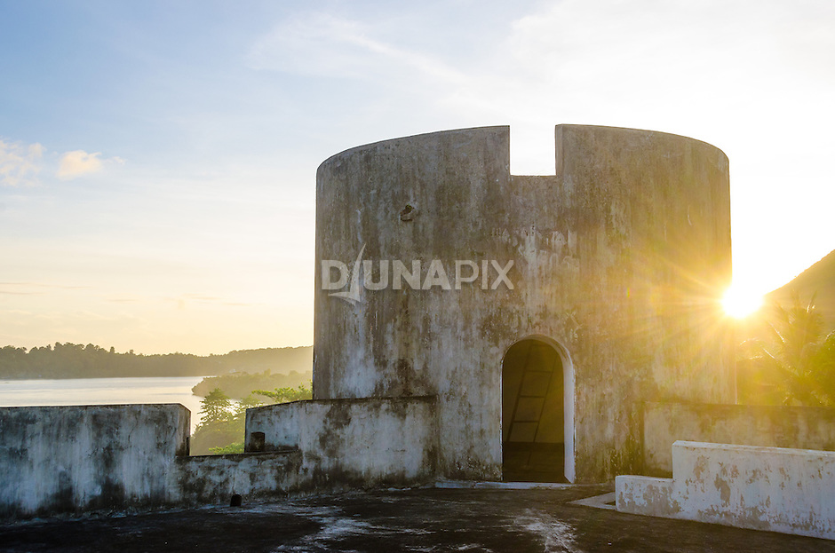 A golden sun sinks behind a watchtower of Fort Belgica, Banda Neira.