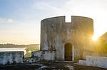 A golden sun sinks behind a watchtower of Fort Belgica, Banda Neira.