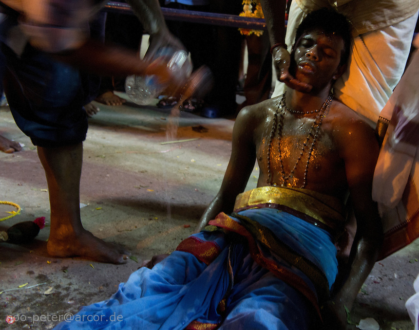 man in trance fainted while Thaipusam ceremonies inside Batu Caves, Kuala Lumpur, Malaysia, 2012. Thaipusam ceremonies, celebrated by tamile Hindu community in Malaysia, take place  in Sanctuary of Batu Caves at the border of Kuala Lumpur, each year around end of January or beginning of February, according to Hindu moon calendar. The event is paying hommage to Lord Murugan, a spirit or god created by Shiva to lead the army of gods against the army of evil demons, finally defeating the evil spirits. There are many ways to present offerings or sacrifices for this major religious event. Devotees mortify their bodies by carrying heavy kavaris with spears fixed in their skin or fruits, flowers and little post with holy milk fixed with hooks in their skin, ascending the stairways to the sanctuary in trance, `followed by assistant  taking care and musicians playing loud and fast rhythmic trance music.  Many families shave their head in a ritual before ascending the stairways, as part of rituals to obtain salvation for their ancestors.