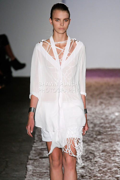 Model walks runway in a white atlyn shirt, and white qawal skirt from the Kimberly Ovitz Spring 2013 runway show at Pier 57, during New York Fashion Week on September 6, 2012.