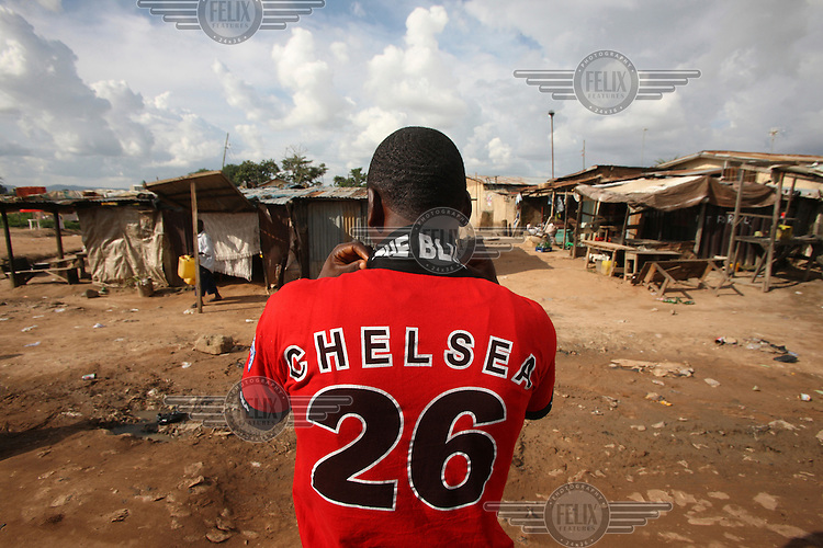 A Chelsea supporter wearing a slightly incongruous red Chelsea shirt walks towards his house in the Gbagi area of Abuja. There are more African players playing in European football leagues then ever before, leading to a decline in interest in local leagues, with fans favouring the more lucrative and 'exciting' European leagues.