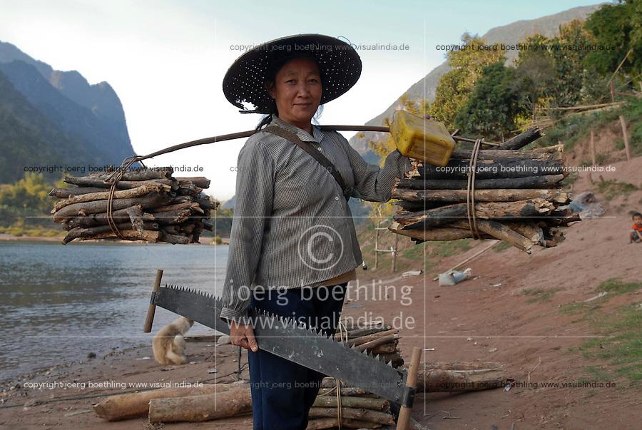 LAOS, village Muang Ngoi at river Nam Ou, a branch of Mekong, Lao Loum woman with firewoods and saw / LAOS, <br /> Dorf Muang Ngoi am Fluss Nam Ou , ein Nebenfluss des Mekong, Lao Loum Frau mit Feuerholz und Saege