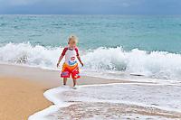 Two year old boy playing on the beach at Playa Bluff Lodge, Bocas del Toro, Colon Island, Panama
