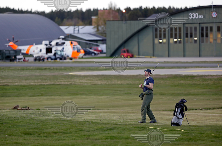 Systems operator Håvard Bakke enjoying a game of golf. Crew from Norwegian Air Force 330 squadron, flying Westland Sea King helicopter. The core mission of the squadron is SAR (search and rescue), but they also fly HEMS (Helicopter Emergency Medical Service), complementing the civilian air ambulance service.<br /> This crew fly out of Rygge Air Station, Norway.