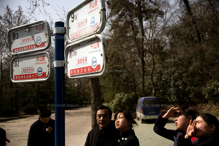 People wait for a bus at a bus stop on Purple-Gold Mountain (also known as Purple Gold Mountain or Zijin Shan in Chinese) in Nanjing, Jiangsu, China.  The mountain is a popular tourist destination and houses Sun Yat-Sen's mausoleum the World Heritage recognized Ming Tombs and other cultural sites.