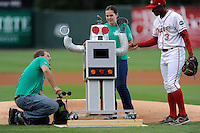 High school students prepare to have their robot throw out the first pitch before a game between the Greenville Drive and Lexington Legends on Monday, August 19, 2013, at Fluor Field at the West End in Greenville, South Carolina. Felix Sanchez (3) of the Drive looks on. (Tom Priddy/Four Seam Images)