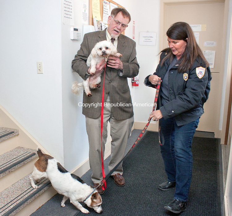 WOODBURY CT- MARCH 21 2014 032114DA10- Woodbury and Bethlehem Animal Control Officer Judy Umstead spends time with Lenny, held by Woodbury's First Selectman William Butterly and Henry, a 5 years old corgi beagle mix as they visit the Woodbury Town Hall on Friday. The dogs are part of the animal cruelty case against Frederick Acker who refuses to sign over the dogs so they can find their deserving homes. The animals have been either in boarding kennels, foster homes or local pounds since November 8, 2012. Judy Umstead along with other supporters have fought back and begun a &quot;Free The 63&quot; campaign to help the dogs.<br /> Darlene Douty Republican American