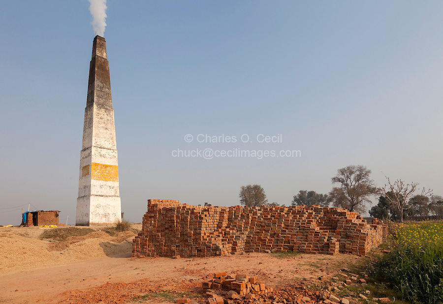 Rajasthan, India.  Chimney Emitting Smoke from Underground Ovens Firing Bricks.