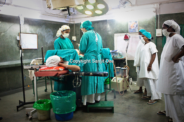 Government nurses (2nd and 3rd from right) undergoing training look over the shoulder of a surgeon who operates a caesarean section on a woman at the operation theatre in Duncan Hospital in Raxaul of East Champaran district of Bihar, India. Since 2008 the Foundation and Geneva Global have been investing in the training of medical staff to improve the lives of people living in 600+ villages in the region. The NGOs are delivering cost effective interventions to address treatment, care and prevention of diseases, disability and preventable deaths amongst infants, adolescent girls and women of child-bearing age. There is statistical and anecdotal evidence that there have been vast improvements and a total of 40-50% increased immunization for all children under 6 has meant that communities can be serviced and educated long term. Photograph: Sanjit Das/Panos for Legatum Foundation