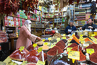 Woman shopper wearing Muslim veil buys spices in Misir Carsisi Egyptian Bazaar food and spice market, Istanbul, Turkey