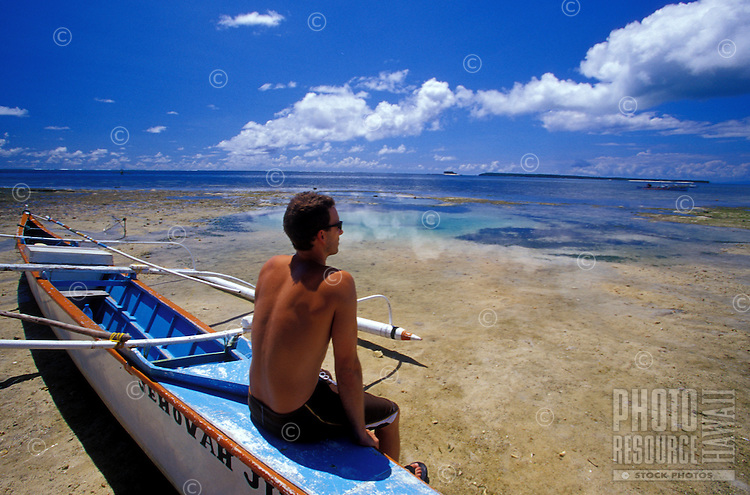 Surfer sitting on local outrigger canoe in clear water on reef, Siargao Island, Philippines