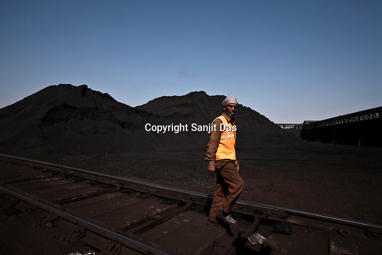 Indian workers seen at the coal deposits of Adani Power at the Mundra Port in Gujarat, India.