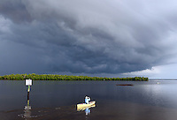 A man paddles his canoe into a bad storm in the Florida Everglades and the 10,000 islands out of Chokoloskee Island. Photo/Andrew Shurtleff