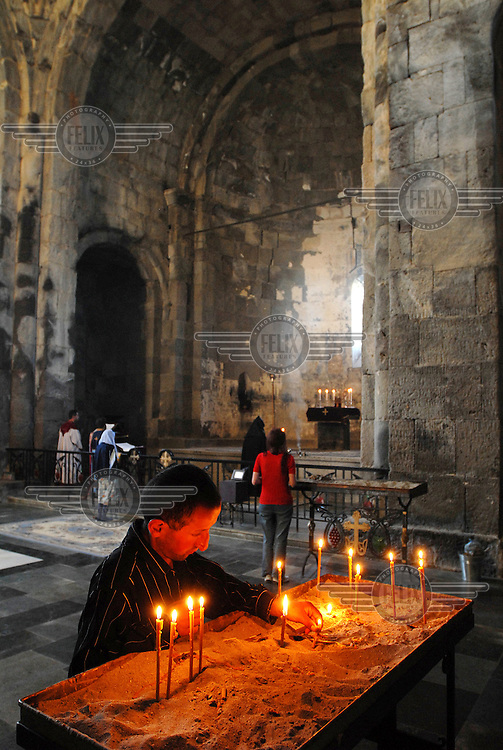 Worshipper lights devotional candles inside the main chamber of the Tatev Monastery.