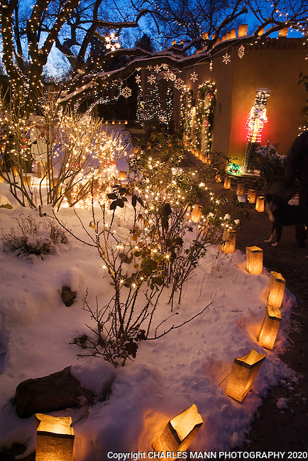 Trees filled with twinkling lights and paper bag faralitos lighting the walkway are all part of the  annual Christmas Eve celebration on Canyon Road in Santa Fe, New Mexico