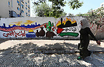Palestinians walk past a mural to mark the 50th anniversary of the burning of Al-Aqsa Mosque, in Gaza City, on August 22, 2019. Photo by Mahmoud Naser
