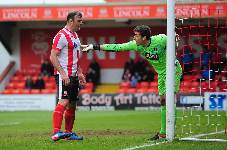 Lincoln City's Matt Rhead tries to block the view of Torquay United's Brendan Moore in the build up to Lincoln City's winning goal, scored by Sam Habergham<br /> <br /> Photographer Chris Vaughan/CameraSport<br /> <br /> Vanarama National League - Lincoln City v Torquay United - Friday 14th April 2016  - Sincil Bank - Lincoln<br /> <br /> World Copyright &copy; 2017 CameraSport. All rights reserved. 43 Linden Ave. Countesthorpe. Leicester. England. LE8 5PG - Tel: +44 (0) 116 277 4147 - admin@camerasport.com - www.camerasport.com