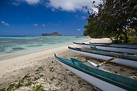 Hawaiian canoes on Waimanalo beach with clear blue water over coral and sand, and a view of Rabbit Island