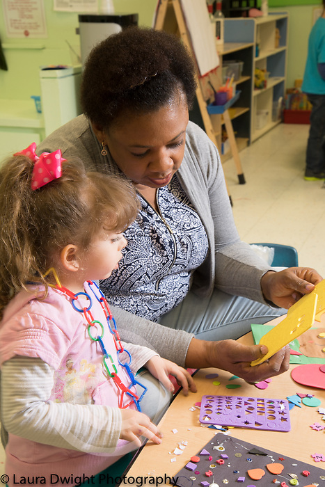Education Preschool 4 year olds teacher working with girl art and fine motor activity gluing collages