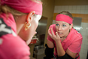 Hot T'Wally of the Hellcats TXRD team puts on makeup before their bout with Putas del Fuego at the Palmer Events Center in Austin, Texas.