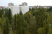 Deserted buildings and the Ferris wheel at the amusement park in Pripyat. <br /> Pripyat was built 1970 as a modern city for personnel at the Chernobyl Nuclear Power Plant a couple of kilometers south. After the nuclear disaster at reactor 4 on April 26 1986, the town's 48.000 inhabitants was evacuated to other parts of the country. Pripiat is today a radioactive ghost town. The whole area is contamined with nuclear material, the half-life of plutonium-239 is more than 24.000 years.<br /> Pripyat, Ukraina.<br /> August 2008.
